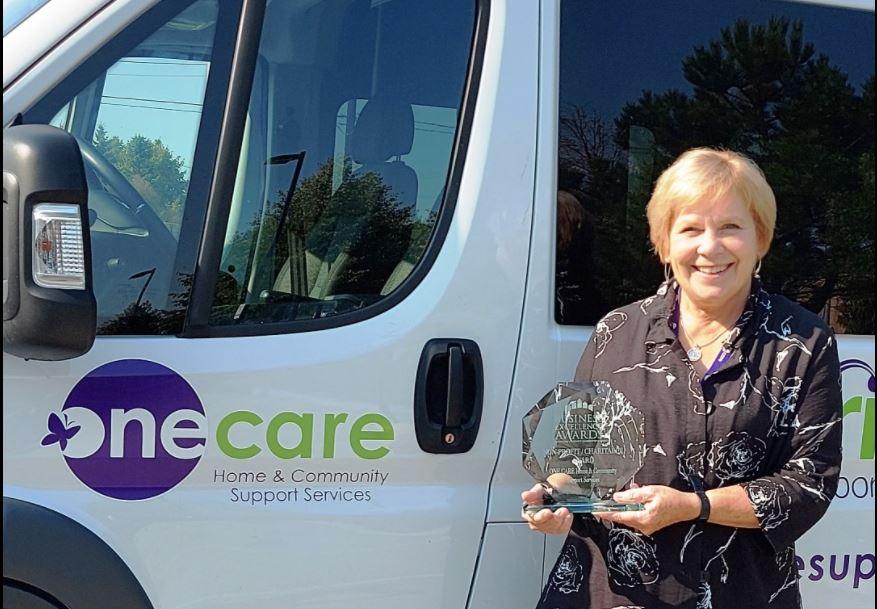 Executive Director, Kathy Scanlon holds award.